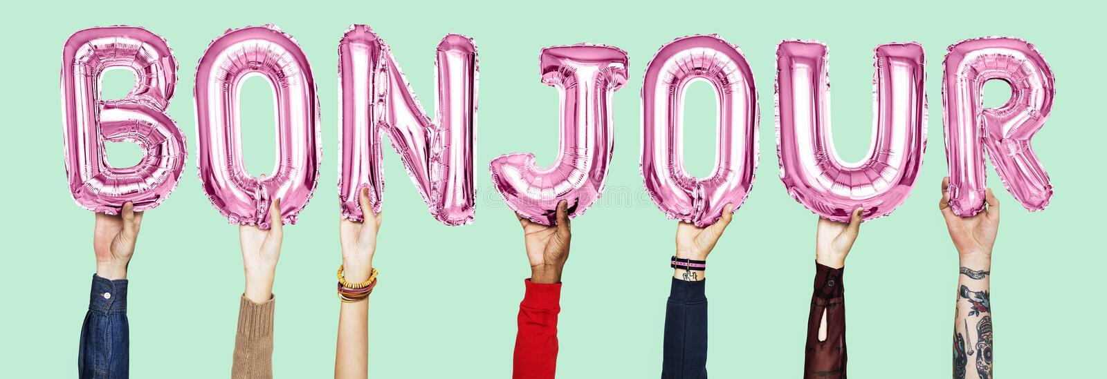 Hands holding Bounjour word in balloon letters stock images