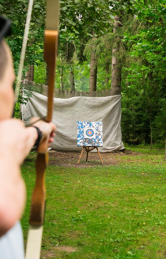 Hands holding a bow with an arrow in front of the target, close-up royalty free stock photo