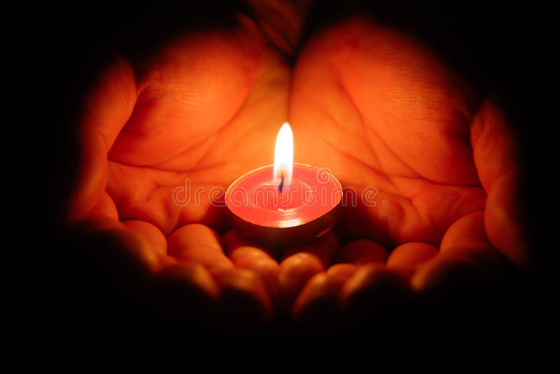 Hands Holding A Burning Candle Stock Photography