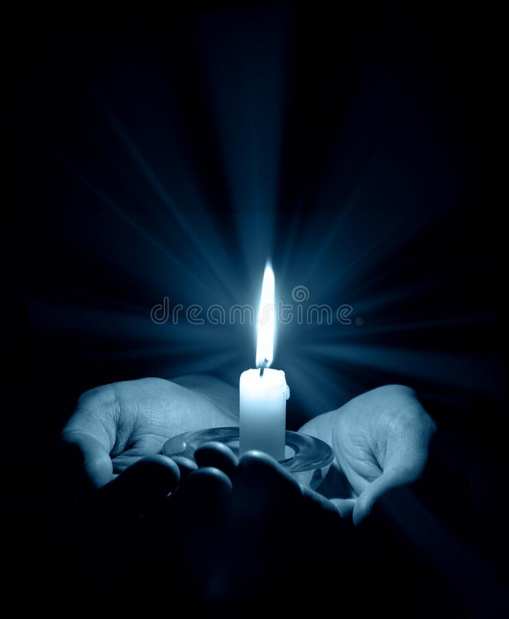 Hands holding a burning candle in dark room stock photos