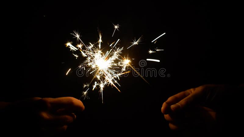 Hands holding burning sparklers or bengal lights. Christmas, new year celebration and pyrotechnics concept - hands holding sparklers or bengal lights burning in stock image