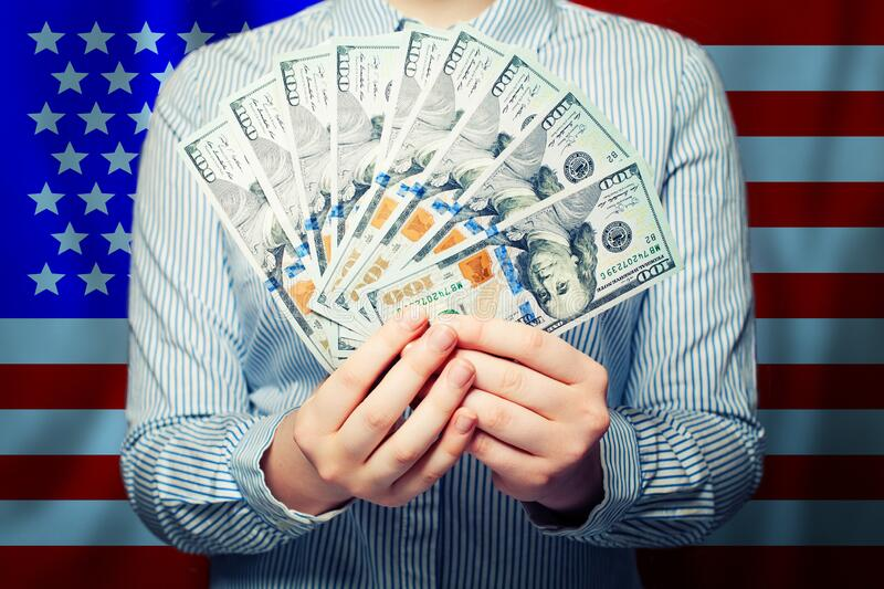 Hands holding cash money us dollars banknote on American flag background.  royalty free stock photography
