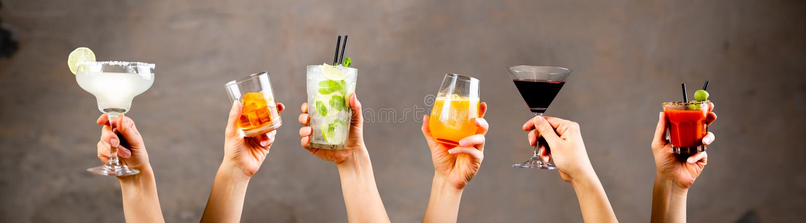 Hands holding classic cocktails on rustic background royalty free stock photography