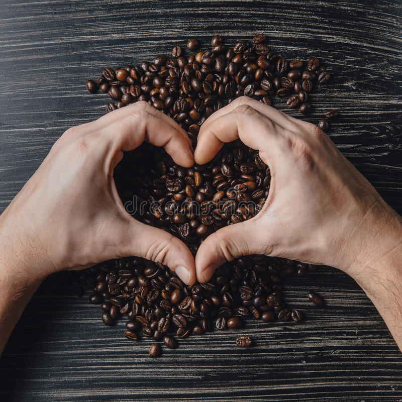 Hands holding coffee beans in shape of heart stock image