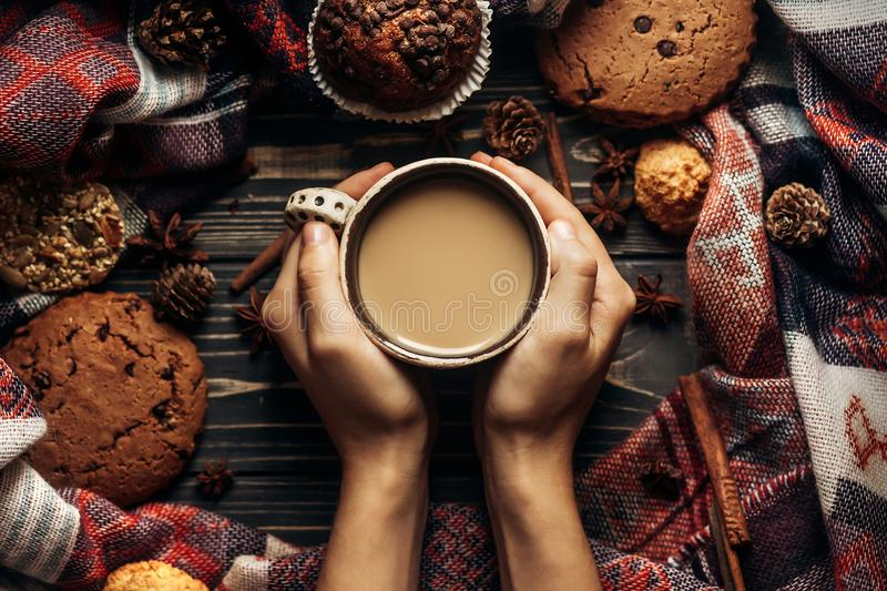 hands holding coffee cookies and spices on wooden rustic background. stylish winter flat lay. space for text. cozy mood autumn. s stock photos