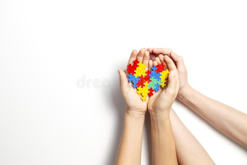 Hands holding colorful heart on white background. World autism awareness day concept royalty free stock photo