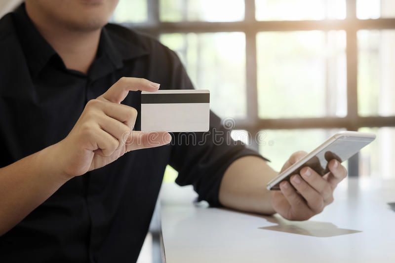 Hands holding credit card and entering security code. royalty free stock image