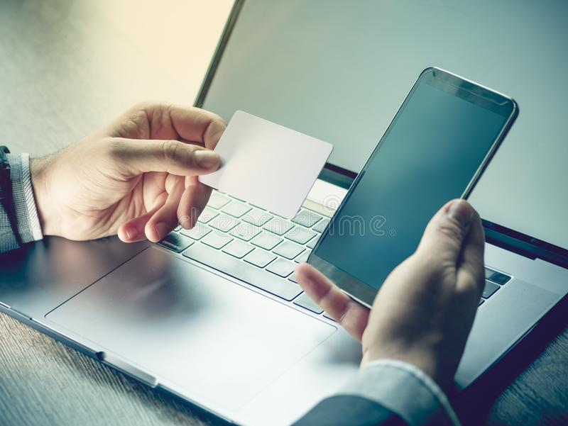 Hands holding credit card, mobile phone and using laptop. Online shopping, Travel booking concept. Selective focus on hand. With card stock photo
