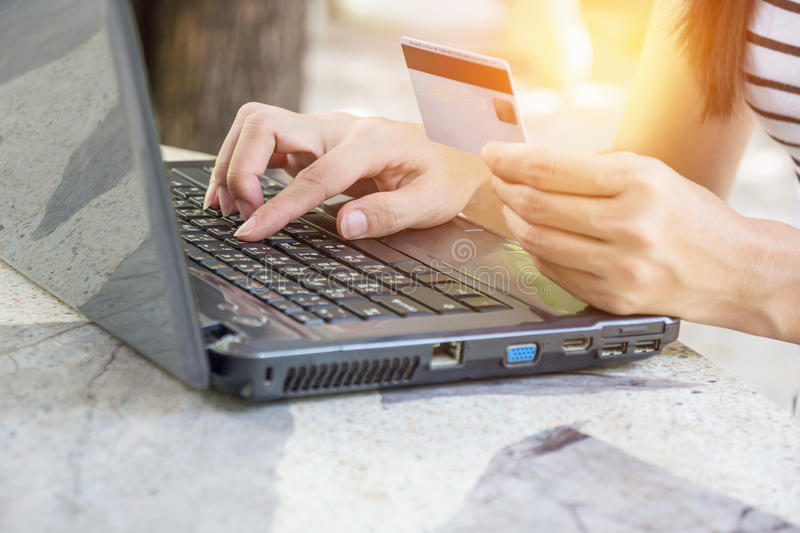 Hands holding credit card and using laptop. Hands holding credit card and using laptop for online shopping stock photography