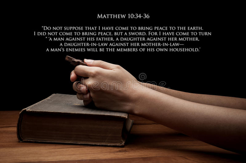 Hands holding a cross on holy Bible with verse stock images