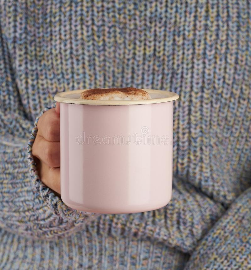 Hands holding cup of hot chocolate, gray cozy sweater, beautiful pink manicure, home style, autumn morning, close up. Hands holding a cup of hot chocolate, gray stock photo