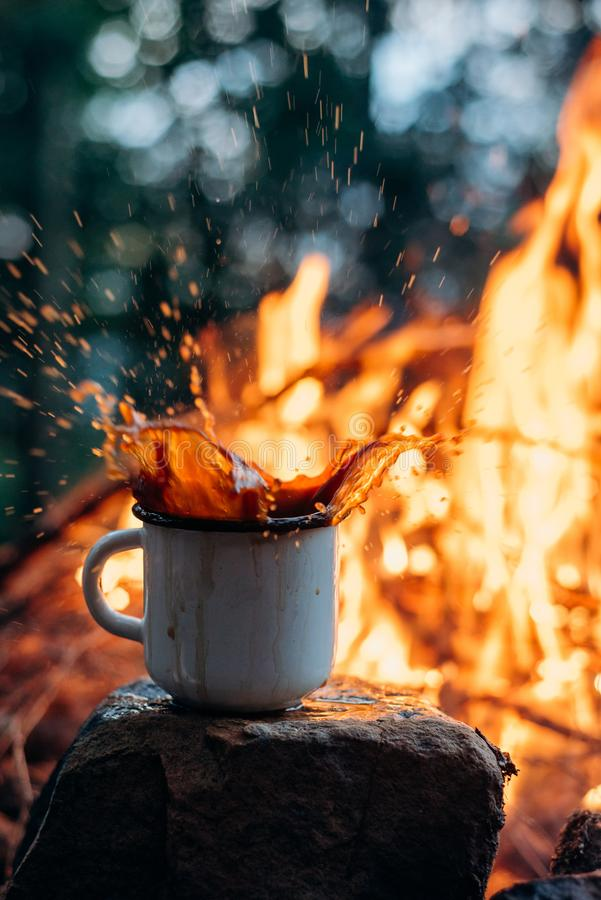 Hands holding cup of tea theHot Coffee cup on the stone near campfire. Evening light. stock photo
