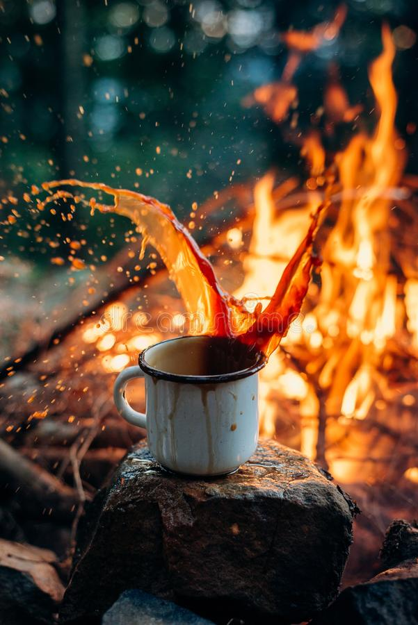 Hands holding cup of tea theHot Coffee cup on the stone near campfire. Evening light. Hot Coffee cup on the stone near campfire. Evening light. Adventure royalty free stock image