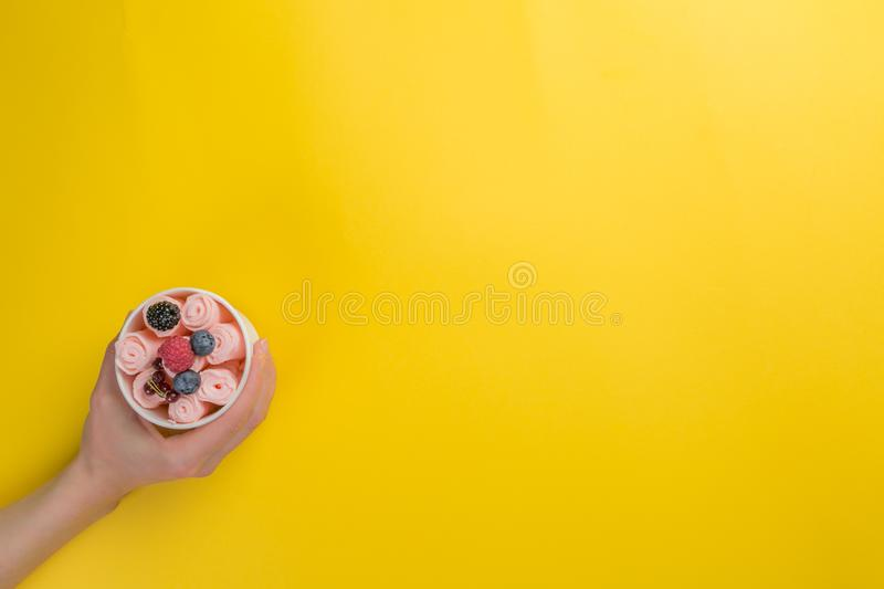 Hands holding cups with different rolled ice cream on bright yellow background stock images