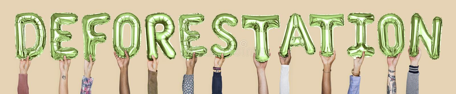Hands holding deforestation word in balloon letters stock images