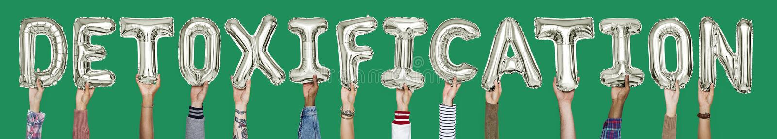 Hands holding detoxification word in balloon letters royalty free stock images