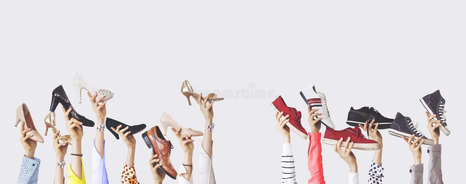 Hands holding different shoes on isolated background stock photo