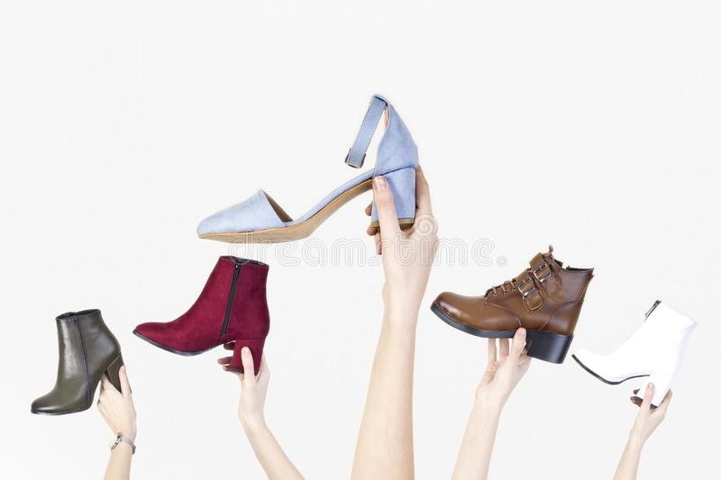 Hands holding different woman shoes on white isolated background. stock image