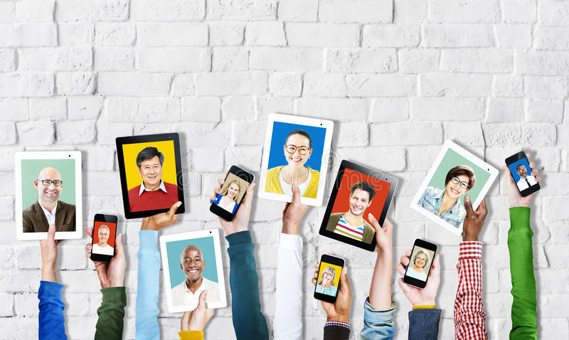 Hands Holding Digital Devices with People's Faces.  stock photography