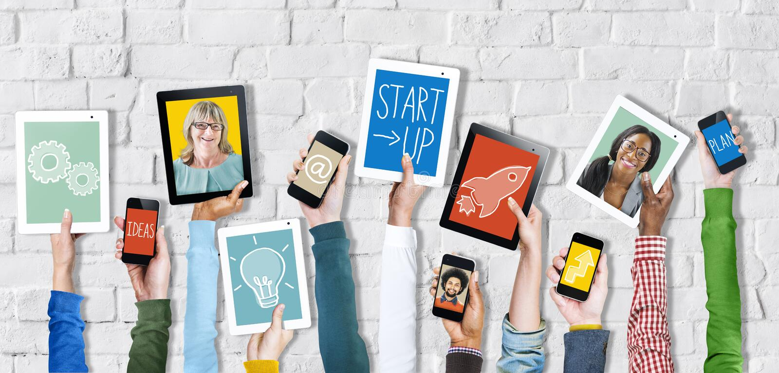 Hands Holding Digital Devices with Startup Concepts. Group of Hands Holding Digital Devices with Startup Concept royalty free stock image