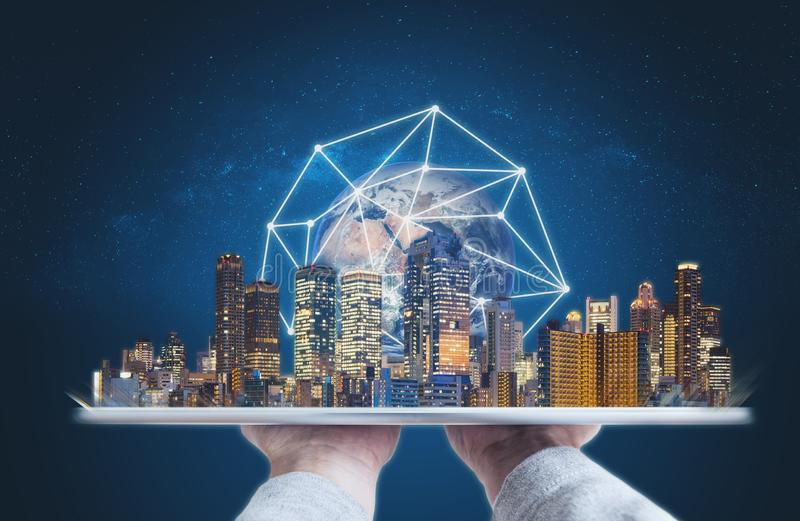 Hands holding digital tablet with modern buildings global network connection technology hologram. Element of this image are furnis. Hands holding digital tablet royalty free stock photography