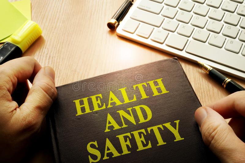 Hands holding documents with title health and safety. royalty free stock images
