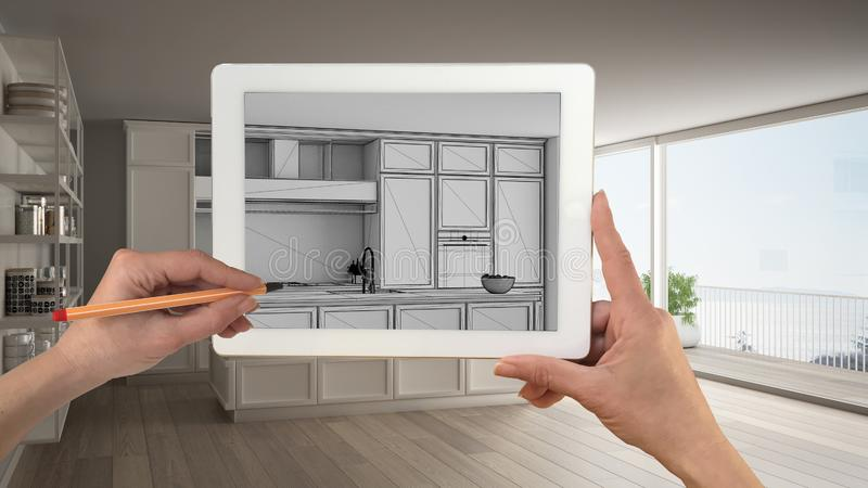 Hands holding and drawing on tablet showing classic white kitchen CAD sketch. Real finished interior in the background, stock images