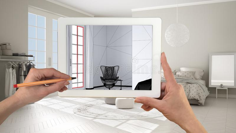 Hands holding and drawing on tablet showing comfortable bedroom with parquet floor and window CAD sketch. Real finished interior royalty free stock image