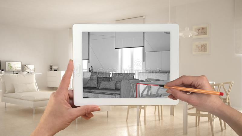 Hands holding and drawing on tablet showing modern living room CAD sketch. Real finished minimalist white project in the backgroun royalty free stock image