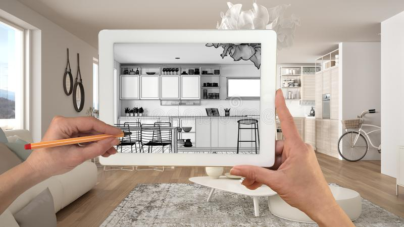Hands holding and drawing on tablet showing modern white kitchen with wooden details CAD sketch. Real finished interior in the royalty free stock image