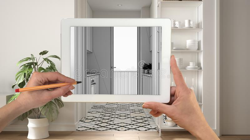 Hands holding and drawing on tablet showing modern white kitchen with wooden details CAD sketch. Real finished interior in the royalty free stock photos