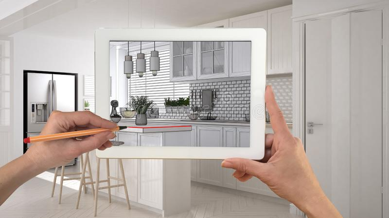 Hands holding and drawing on tablet showing scandinavian white kitchen with wooden details CAD sketch. Real finished interior in stock photo