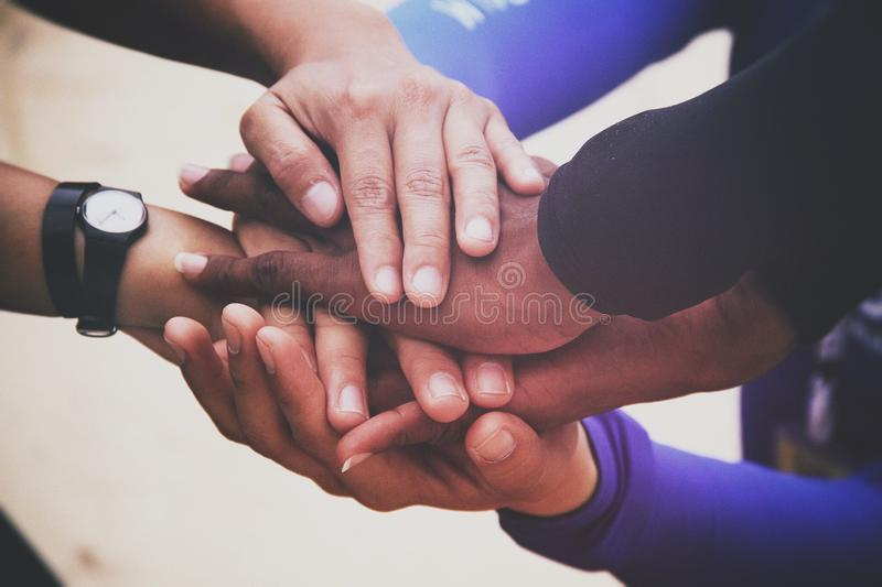 Diverse group of people holding hands in supportive gesture stock image