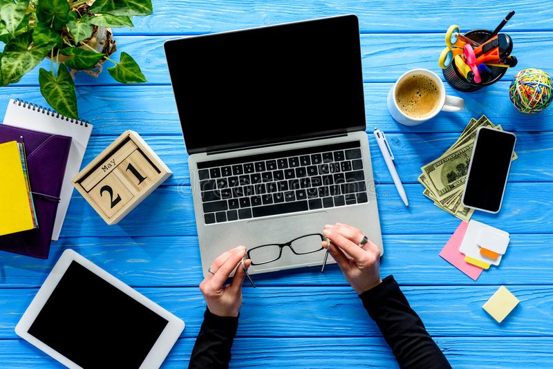 Hands holding eyeglasses by laptop on blue wooden table with stationery. And money stock photos