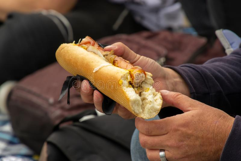 Hands holding a fast food snack - the traditional hotdog with mustard at street food festival. American, background, cook, grilled, lunch, meal, meat, sausage royalty free stock photos