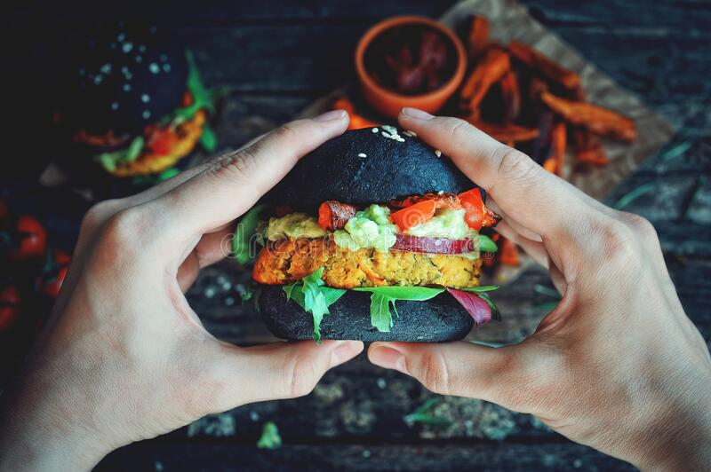 Hands holding fresh chickpea black vegan burger royalty free stock image
