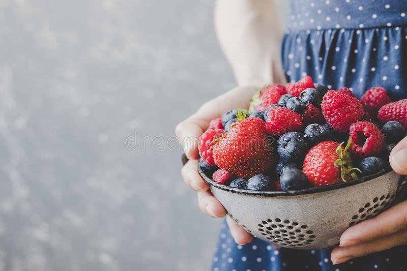 Hands holding fresh juicy berries. Summer background with copy space stock image