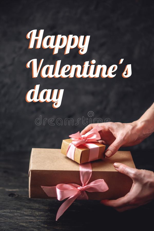 Hands holding gift box Packed in Kraft paper on dark background. Holiday vertical card Happy Valentine`s day with text stock images