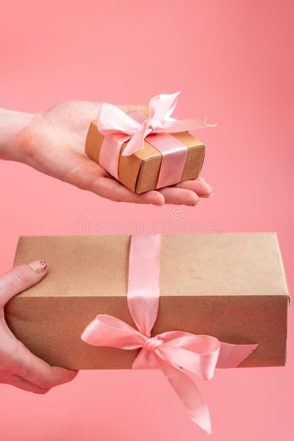 Hands holding gift box Packed in Kraft paper on pink background. Holiday card for Valentine`s day and women`s day stock photos