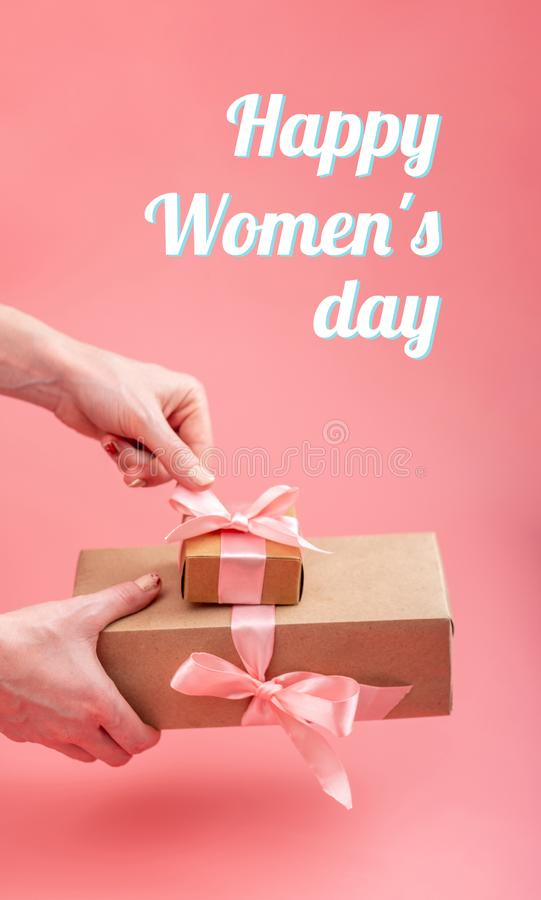 Hands holding gift box Packed in Kraft paper on pink background. Holiday vertical card Happy Women`s day with text stock images