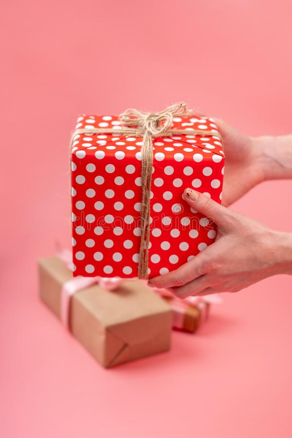 Hands holding gift box Packed in red polka dot paper on pink background. Holiday card for Valentine`s and women`s day stock photo