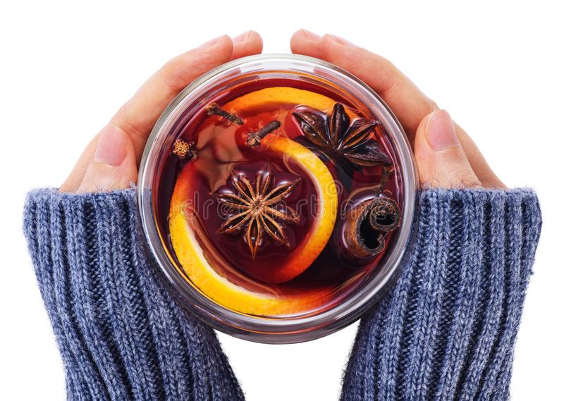 Hands holding a glass cup with mulled wine royalty free stock photos