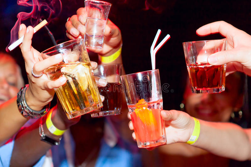 Hands holding the glasses of cocktail and vodka royalty free stock photos