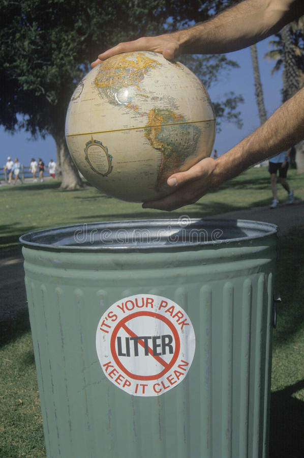 Hands holding a globe over a park trash receptacle royalty free stock photos