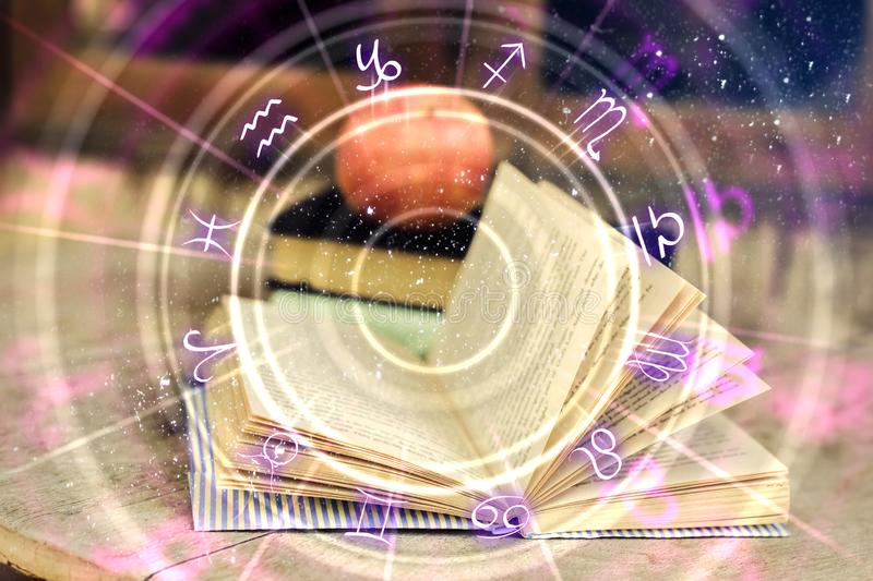 Hands holding glowing zodiac wheel book. Close up of hands holding glowing book with zodiac wheel. Magic and astrology concept. Double exposure royalty free illustration