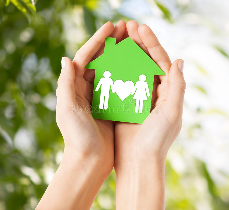 Hands holding green house with family stock photo