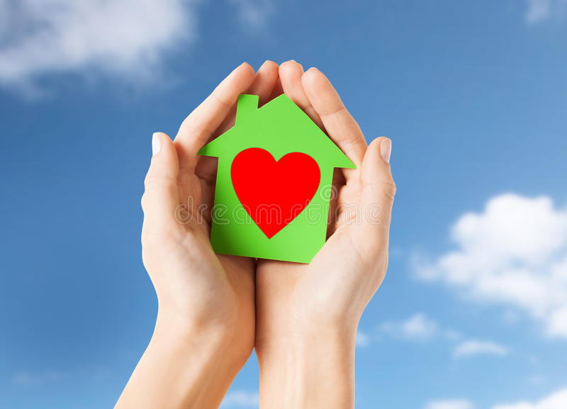 Hands holding green paper house with heart shape. Charity, real estate and love concept - close up of female hands holding green paper house with red heart shape royalty free stock images