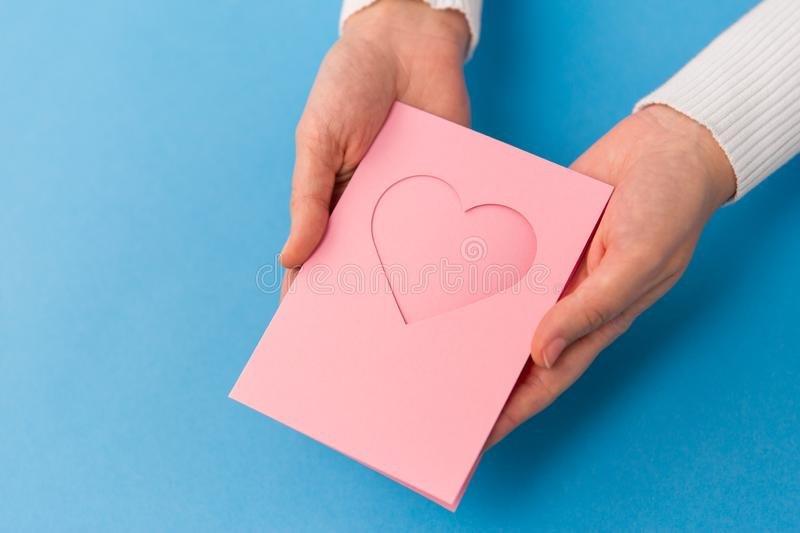 Hands holding greeting card with heart. Holiday, love and valentines day concept - close up of hands holding greeting card with heart on blue background royalty free stock photo