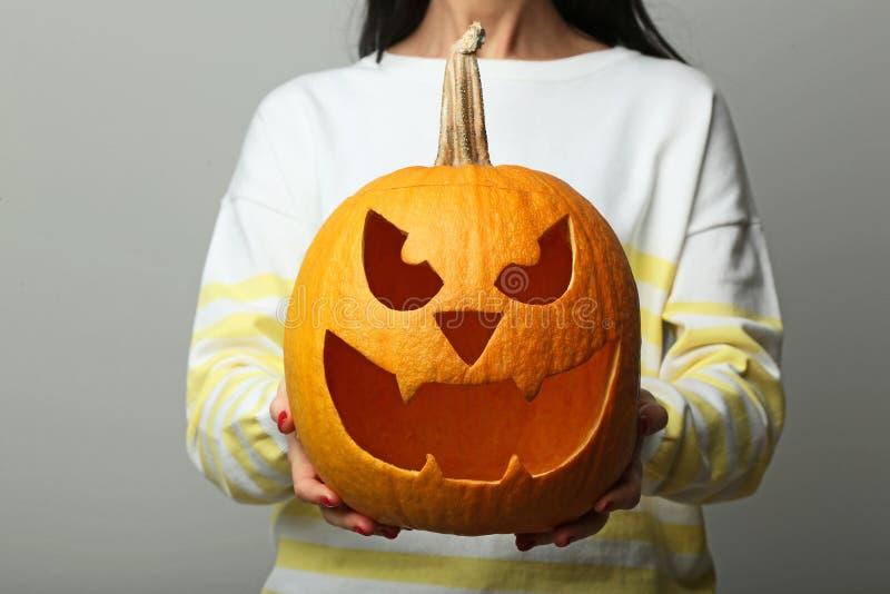 Hands holding halloween pumpkin. Female hands holding halloween pumpkin on grey background stock photography