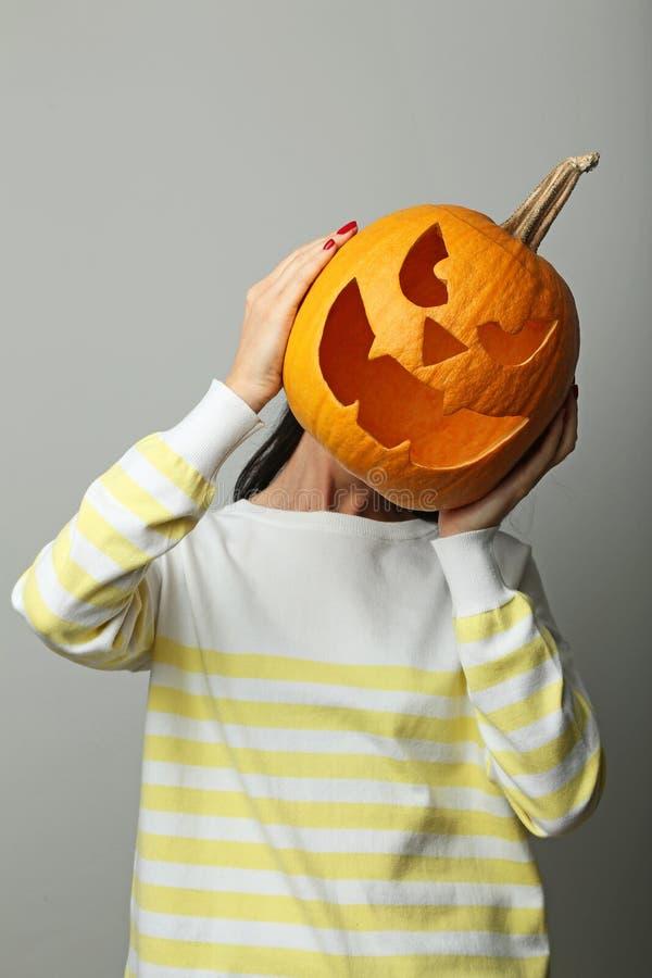 Hands holding halloween pumpkin. Female hands holding halloween pumpkin on grey background stock photo